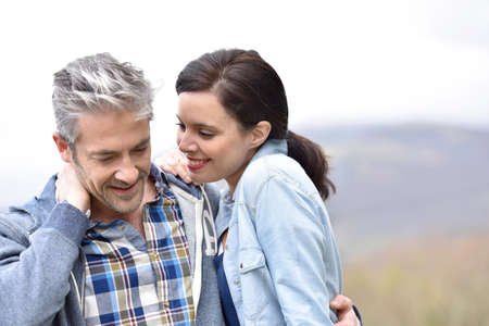 middleaged: Cheerful middle-aged couple embracing outside