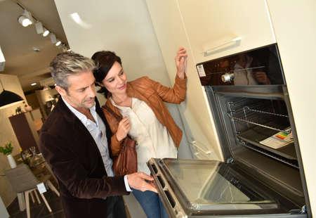 Paar in keukenmeubelen winkel op zoek naar apparaten Stockfoto