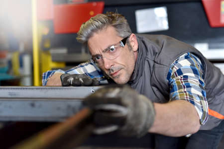 Industrial workers: Metalworker checking piece of iron in workshop