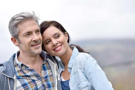 Fröhlich Paar mittleren Alters umarmen draußen