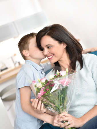 mom son: Son kissing mom on her birthday