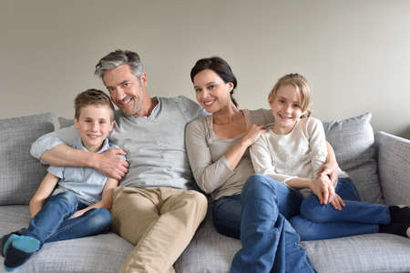 four people: Portrait of happy family sitting in sofa