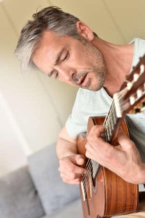 guitars: Man playing acoustic guitar at home Stock Photo