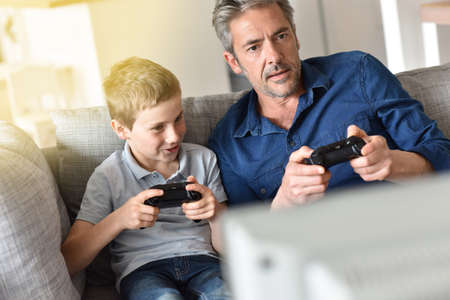 playing video game: Father and son playing video game on tv
