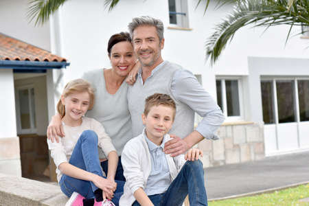 front house: Happy family standing in front of new house