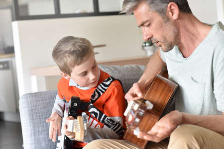father and son: Daddy with son playing the guitar