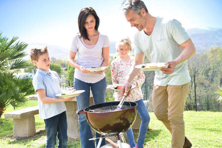 house family: Family having barbecue lunch in garden