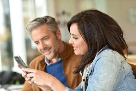 persona feliz: Pareja mayor uso de teléfonos inteligentes en cafetería