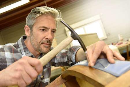 upholsterer: Man working in upholstery workshop Stock Photo