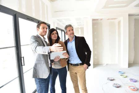 Pares con el agente de bienes raíces visitando la casa en construcción