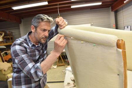 Hombre que trabaja en el taller de tapicería Foto de archivo