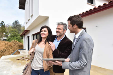 Paar met makelaar een bezoek aan huis in aanbouw Stockfoto