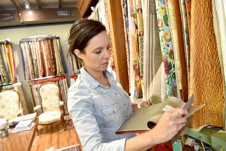 La donna in negozio di tappezzeria guardando campioni