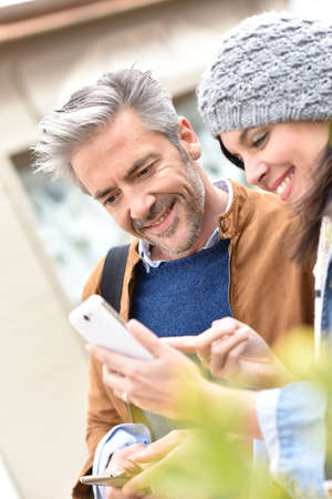 websurfing: Trendy mature couple in town using smartphone
