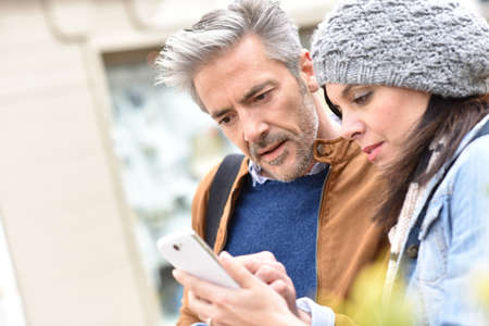 brunette woman: Trendy mature couple in town using smartphone