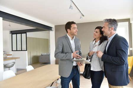 Pareja madura con el agente de bienes raíces de visitar la nueva casa