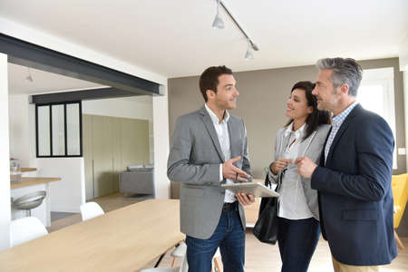 Starší pár s realitním agentem návštěvě nový dům Reklamní fotografie - 55298919