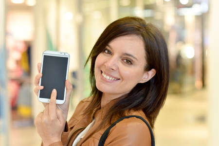 showing: Woman in shopping mall showing smartphone Stock Photo