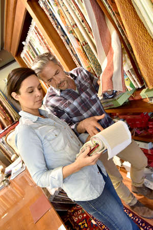 upholsterer: People in upholstery shop choosing sample Stock Photo