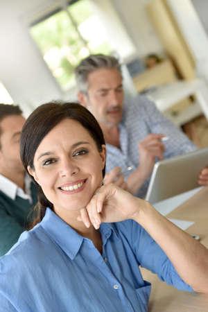 attending: Smiling businesswoman attending meeting