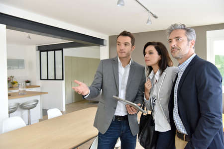 realestate: Mature couple with real-estate agent visiting new house Stock Photo