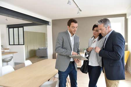 Pareja madura con el agente de bienes raíces de visitar la nueva casa Foto de archivo