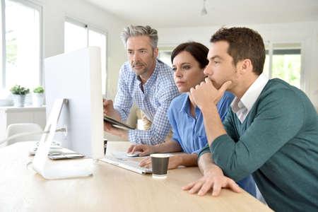 Ludzi biznesu pracujących na komputerze stacjonarnym