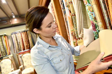 upholsterer: Woman in upholstery shop looking at samples