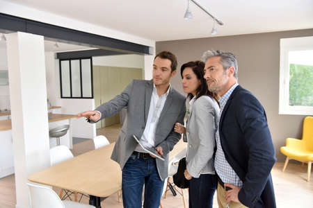 Mature couple with real-estate agent visiting new house Stock Photo