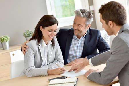 Paar in immobiliën agentschap contract ondertekent Stockfoto