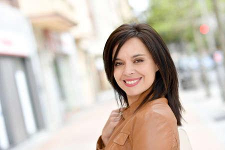 Lachende actieve vrouw die in de straat loopt