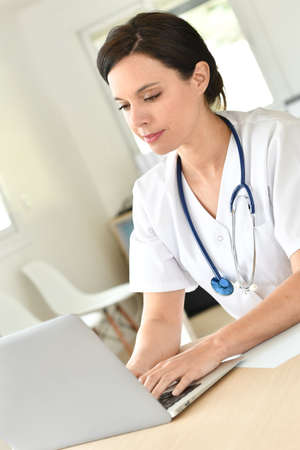 working on computer: Doctor working on laptop computer
