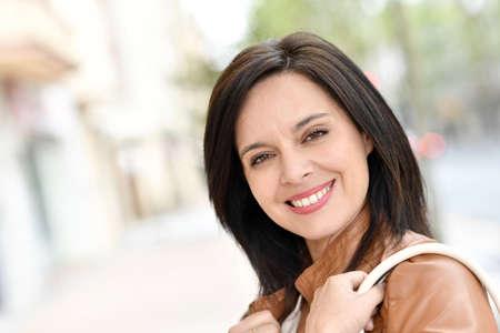 mujer activa que camina en la calle sonriendo Foto de archivo