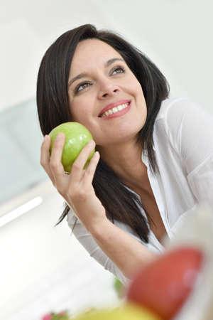 manzana verde: Mujer madura hermosa que come la manzana verde