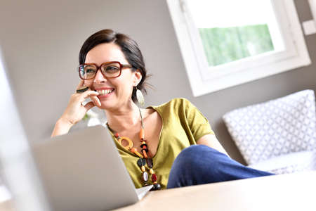 home business: Trendy woman working on laptop from home