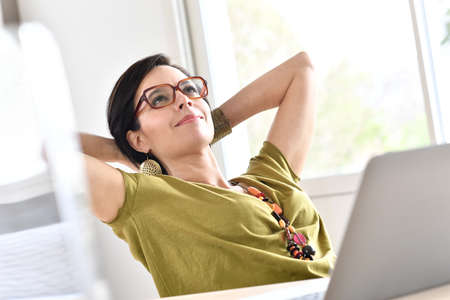homeoffice: Trendy businesswoman relaxing in front of laptop