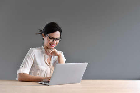 working on laptop: Attractive woman working on laptop computer Stock Photo