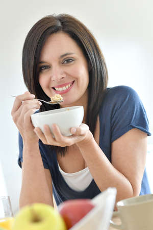 woman eating: Portrait of mature woman eating cereals