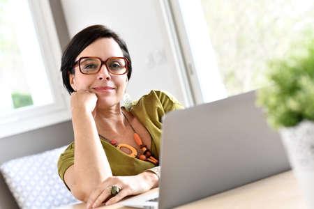 trabajando en casa: Mujer de moda que trabaja en la computadora portátil del hogar Foto de archivo