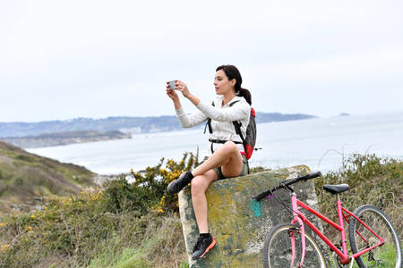 middleaged: Woman on biking day taking picture with smartphone Stock Photo