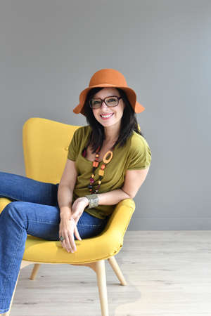 girl in a hat: Trendy woman with hat sitting on yellow armchair, isolated Stock Photo