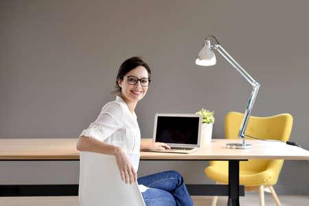 femme brune: jeune fille assise dans le bureau de travail à la mode
