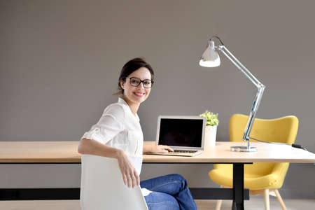 chairs: Trendy working girl sitting in office Stock Photo