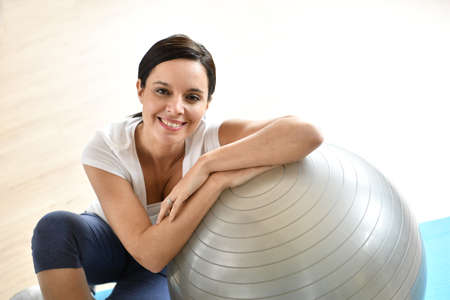 upper floor: Mature woman sitting by fitness ball Stock Photo