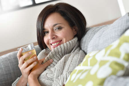 woman portrait: 40-year-old woman relaxing in sofa with cup of tea