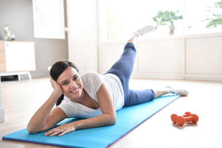 pretty brunette woman: Woman doing workout exercises at home
