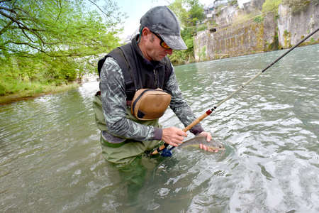 caught: Fly-fisherman holding fario trout caught in river