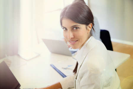 shared: Businesswoman working on laptop, shared workspace