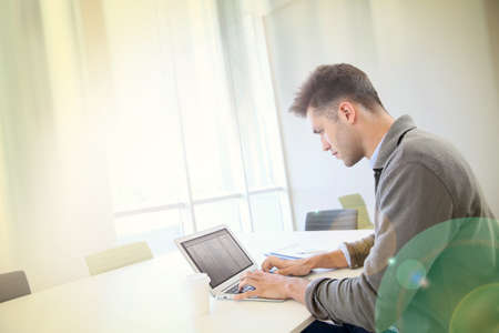 computer room: Businessman using laptop in contemporary working room