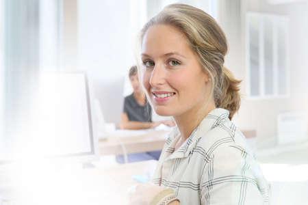 blond girl: Portrait of student girl working on desktop computer